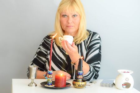 Photo pour Middle age beautiful woman guessing on the coffee grounds, concept of divination, fortune telling and clairvoyance. Selective focus of hand holding cup with coffee grounds. - image libre de droit
