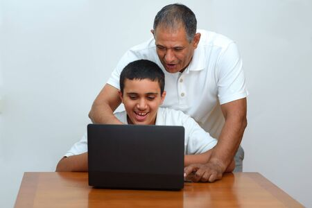 Foto de Senior Father and teenage son using laptop. Boy and dad sitting at home working with tablet computer.Happy family old grandfather and grandson on laptop.Elderly teacher trainer and teen pupil boy. - Imagen libre de derechos