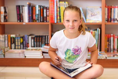 Photo pour Teenager girl in library in front of books. Cute young child sitting on floor and reading book. Little kid reads in a bookstore, surrounded by colorful books. Library, Shop, Shelving In Home. - image libre de droit