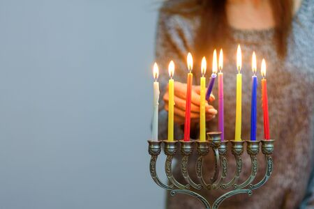 Photo for Jewish Woman lighting Hanukkah Candles in a menorah. People celebrate Chanukah by lighting candles on a menorah, also called a Hanukiyah. Each night, one more candle is lit. - Royalty Free Image