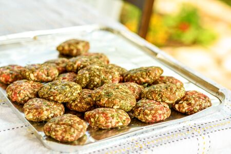 Photo pour Raw homemade kebab or meatball with green parsley, garlic, spices and sliced onion. It is a very popular in Middle East. BBQ outdoor party. - image libre de droit