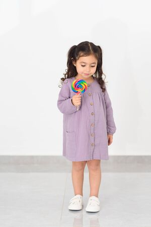 Photo pour Beautiful little girl with lollipop on white background in home. - image libre de droit