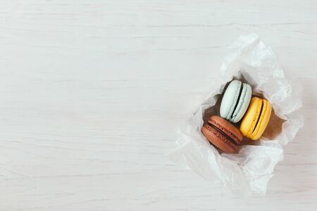 Photo pour Three French macarons in gift box on a white wooden table. Chocolate, yellow and light blue macarons. Place for text. - image libre de droit
