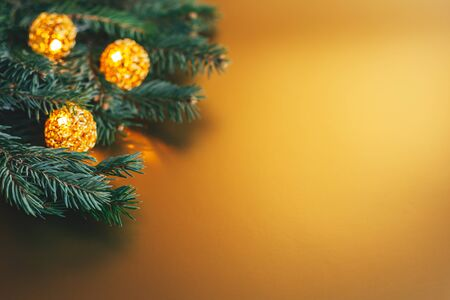 Photo pour Fluffy branches of a spruce or fir-tree with christmas lights on golden background. Christmas wallpaper or postcard concept. Selective focus. Close-up. Place for text. - image libre de droit