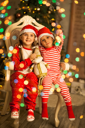 Photo pour Happy little kids in matching red striped pajamas in beautiful living room. Happy friends sit together on a chair near the Christmas tree and hold the toys in their hands on Xmas eve. - image libre de droit