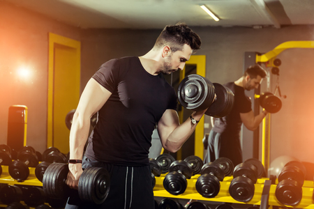 Foto de Concept Power Strength Healthy Lifestyle Sport Powerful Muscular man working out in gym doing exercises at biceps with dumbbells - Imagen libre de derechos