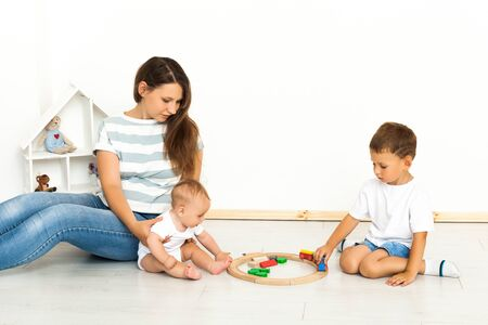 Photo for Motherhood. Spending time together. Mother Sitting With kids playing toys Indoors at home - Royalty Free Image