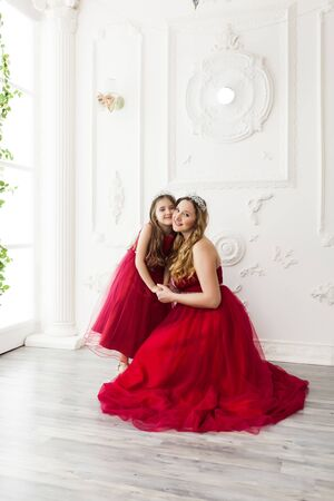 Photo pour Mother and daughter in same outfits posing in the interior of the photo studio weared Red Dresses. Family look - image libre de droit