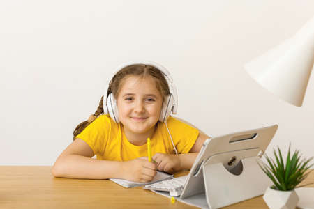 Foto de Caucasian Little girl in headphones sit at desk writing in notebook studying online at home, little child handwrite prepare homework on quarantine, have web lesson indoors. Covid-19 coronavirus. - Imagen libre de derechos