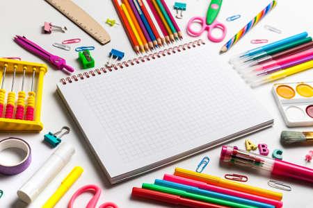 Foto de School office supplies on a desk with copy space. Back to school concept. Blank notebook with colourful school supplies - Imagen libre de derechos