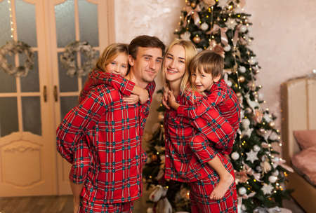 Foto de Big four members family in red pajams. Daddy mommy and two children spending x-mas time together piggyback riding and having fun at home - Imagen libre de derechos
