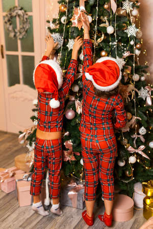 Photo pour Happy little Two kids in red plaid pajamas and hats decorate the Christmas tree in beautiful living room. - image libre de droit
