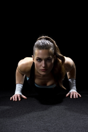 fit woman doing pushups on black background