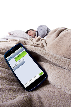 cell phone screen showing text messages while male is in bed