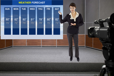 young woman on stage with weather chart and camera