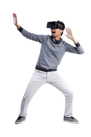Male immersed in interactive virtual reality video game doing gestures on white background