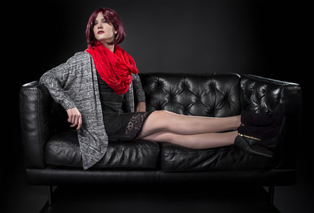 Fashionable female sitting and resting on a comfortable black leather couch