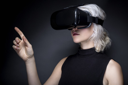 Photo pour Woman wearing a virtual reality headset touching or holding something.  She is interacting with something she is watching or playing a video game.  The image depicts VR and AR technology. - image libre de droit