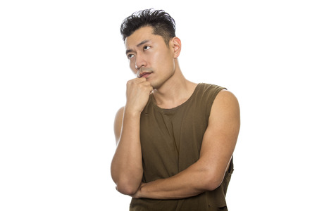 Athletic Asian male with trendy torn sleeveless shirt on a white background.  He is displaying confused or thinking expressions or gestures.  The handsome chinese or japanese man is muscular and physically fit