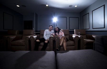 Photo pour Interracial couple on a movie date in a living room with a home theater system with seats.  They are drinking red wine on glass.  They are watching a movie or television. - image libre de droit