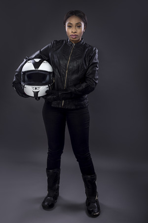 Photo for Black female motorcycle biker or race car driver or stuntwoman wearing leather racing suit and holding a protective helmet.  She is standing confidently in a studio - Royalty Free Image