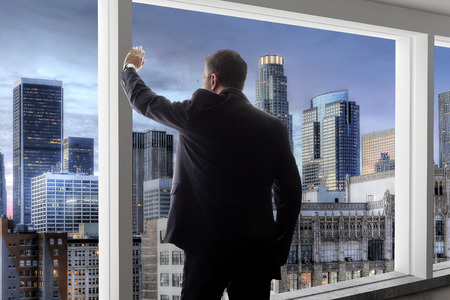 Photo pour Middle aged businessman looking out a bright office window in Los Angeles and thinking - image libre de droit