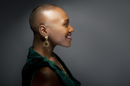 Photo pour Black African American female fashion model with a bald hairstyle in a studio.  The portrait shows the beauty and confidence of the bold and trendy glamour hairdo style. - image libre de droit