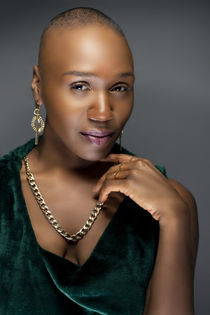 Photo pour Beautiful black African American female model posing confidently with bald hairstyle in a studio.  The woman is wearing stylish fashion and portraying uniqueness and individuality. - image libre de droit