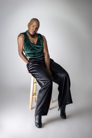 Photo pour Black African American female fashion model wearing trendy green outfit and heels sitting on a stool.  She is confidently showing off a bold bald hairstyle.   - image libre de droit