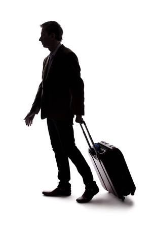 Photo pour Silhouette of a businessman going on a business trip and traveling with luggage.  The man is carrying bags like preparing to board a flight at an airport.  - image libre de droit