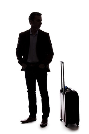 Photo pour Silhouette of a traveling businessman going on a business trip.  He is waiting with luggage as if he is in the airport departure or arrival. Isolated on white background for composites. - image libre de droit