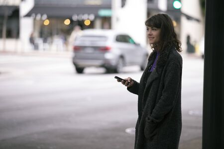 Female pedestrian waiting on a sidewalk for a rideshare.  She is sharing her gps location via cellphone app so the driver can pick her up in the city.  Cars are blurred to obscure make model and license plates.