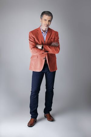 Photo pour Middle-aged fashion model wearing coral colored sports coat or jacket for the fall clothing collection.  Depicts modern colorful apparel style for 2019. - image libre de droit