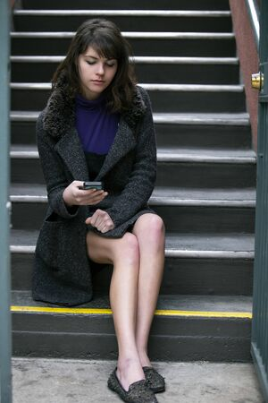 Young female millennial waiting outside apartment home by the stairs for a rideshare or taxi cab.  She is holding her mobile phone and messaging or using app.