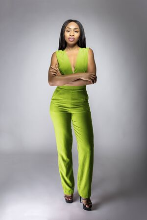 Photo pour African American fashion model posing with lime green v-neck jumpsuit in a studio for fall collection catalog.  She is confidently showing the sleeveless top and matching pants. - image libre de droit