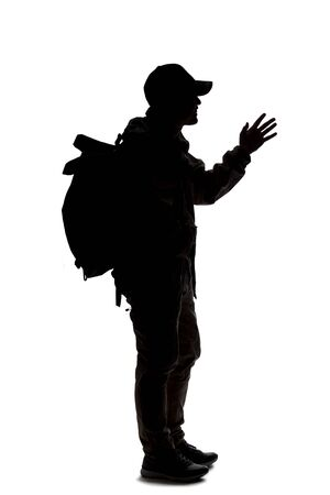 Photo pour Silhouette of a man wearing a backpack looking like a traveler or hiker trekking.  He is gesturing like he is talking or speaking - image libre de droit