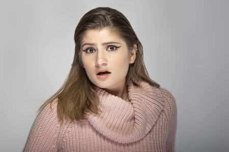 Photo pour Close up portrait of a young Caucasian woman wearing a pink sweater on a grey background.  The model looks shocked and scared - image libre de droit
