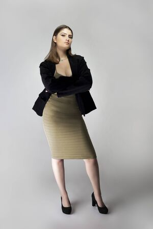 Photo for Female model posing as a sexy business woman looking confident like a boss or a manager. Her outfit is a trendy brown or tan dress with a business suit or jacket.  - Royalty Free Image