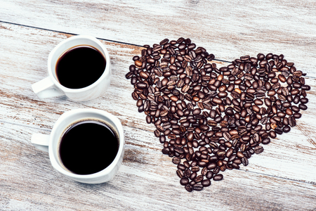 two cups of coffee with beans in the shape of the heart