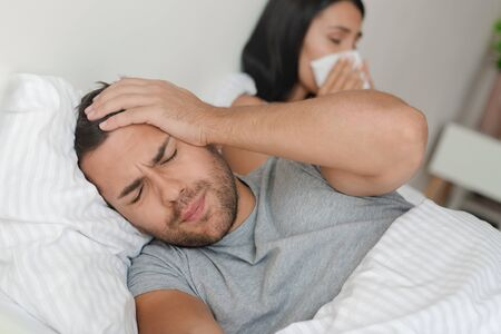 Photo for Young couple having flu and lying in bed at home. Man have headache while his wife sneezing at napkin - Royalty Free Image