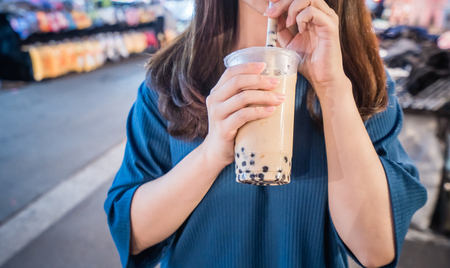 Foto de A young woman is drinking a plastic cup of bubble milk tea with a straw at a night market in Taiwan, Taiwan delicacy, close up. - Imagen libre de derechos