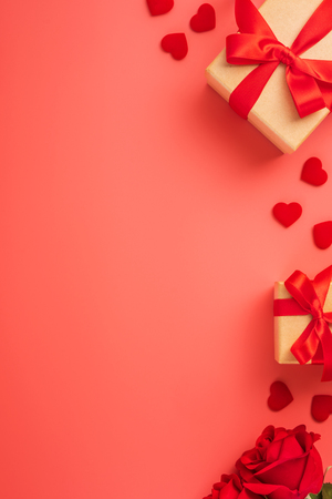 Foto de Gift box with red ribbon and rose in trendy colour of 2019 living coral, concept of Valentine's, anniversary, mother's day, copy space, top view. - Imagen libre de derechos