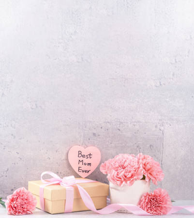 Foto de May mothers day handmade giftbox wishes photography - Beautiful blooming carnations with pink ribbon box isolated on fair-faced gray background desk, close up, copy space, mock up - Imagen libre de derechos