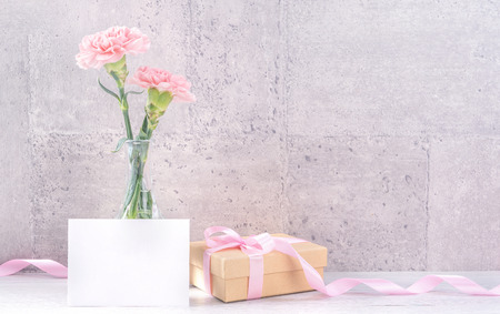 Foto de Beautiful blooming carnations with pink ribbon box isolated on fair-faced gray background desk - Imagen libre de derechos