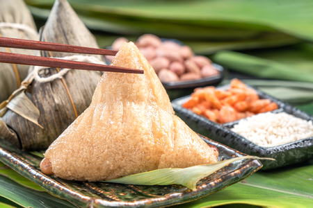 Foto de Close up, copy space, famous asian tasty food in dragon boat (duan wu) festival, steamed rice dumplings pyramidal shaped wrapped by bamboo leaves made by sticky rice raw ingredients - Imagen libre de derechos