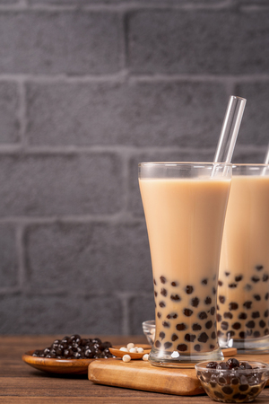 Photo for Delicious bubble milk tea with straw in drinking glass on wooden table background, concept of reduce plastic to go in Taiwan, close up, copy space - Royalty Free Image