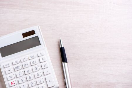 Photo for White calculator and pen on bright wooden table, analytics and statistics of financial profit, investment risk concept, copy space, top view flat lay - Royalty Free Image