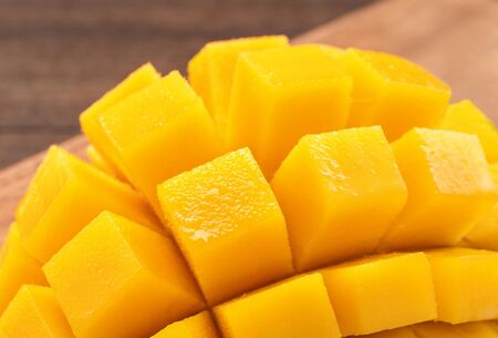 Photo for Fresh chopped mango cubes on wooden cutting board and rustic timber background. Tropical summer fruit concept, close up, macro, copy space. - Royalty Free Image