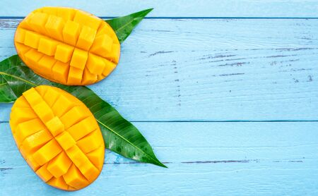 Photo pour Fresh chopped mango with green leaves on bright blue timber background. Top view, flat lay, copy space. Tropical fruit concept. - image libre de droit