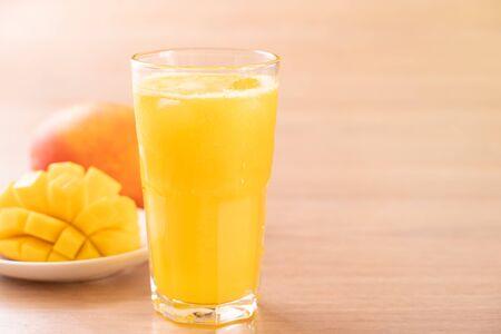 Photo pour Fresh mango juice with beautiful chopped pulp flesh on bright wooden table background. Tropical fruit drink design concept. Close up, copy space. - image libre de droit